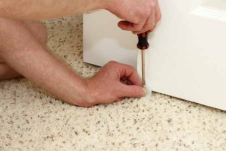 closet door: Caucasian hands of an adult male using a screwdriver to secure a white plastic closet door guide into a carpeted floor of a home. Securing a closet door floor guide