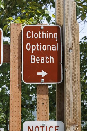 optional: On a wooden post is a brown and white metal Clothing Optional Beach sign on wooden posts outside with foliage in the background on a sunny day.