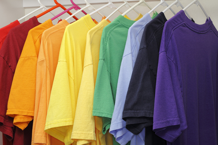 Many different colors of t-shirts hanging in a closet. A rainbow variety of ten different colors of casual mens t-shirts. Stockfoto