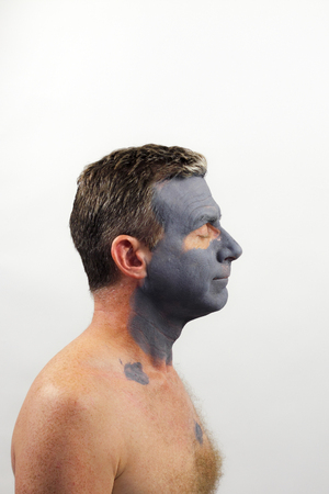One shirtless caucasian man right side view wearing a drying dark gray charcoal tea tree oil face mask as a treatment for his facial skin. A man wearing a clay beauty mask photo