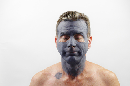 late forties: Male in his late forties wearing a charcoal and bentonite clay face mask beauty treatment. Front portrait of a white male wearing a bentonite mud mask beauty treatment.