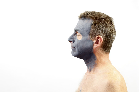 forties: Adult male in his forties facing left wearing a dark gray charcoal and bentonite mud mask. A guy with a charcoal and bentonite mud mask skin treatment on his face Stock Photo