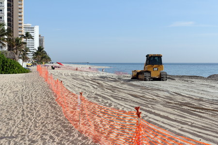 widening: Fort Lauderdale, FL, USA - March 3, 2016: Fenced in beach with a bulldozer replenishing sand in a nourishment project. An earth mover spreads beach restoration sand