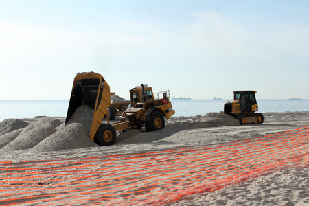 widening: Fort Lauderdale, FL, USA - March 3, 2016: Two dump trucks and a bulldozer work on beach nourishment on the coast. Earth moving equipment add sand to a public beach.