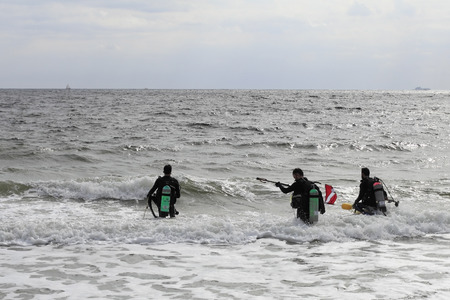 Fort Lauderdale, FL, USA - March 5, 2016: Three male scuba divers walk into the Atlantic Ocean to go diving. Divers with full gear head into the ocean to go diving Editorial