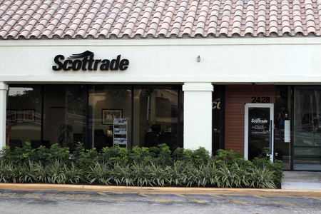 outdoor outside: Fort Lauderdale, FL, USA - April 26, 2016: Small outdoor Scottrade sign above a covered walkway. Scottrade sign and office entrance outside during the early morning.