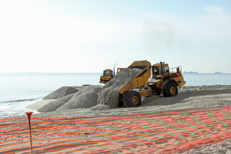 widening: Fort Lauderdale, FL, USA - March 3, 2016: Piles of sand dumped on the beach shore replenish and widen. Large trucks restore sand on the coast expanding the beach.