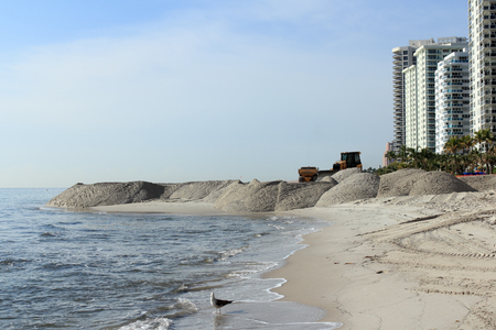 widening: Fort Lauderdale, FL, USA - March 3, 2016: Large sand piles distributed on the shores widening the beach. Shore beach expansion  machinery spreading the sand.