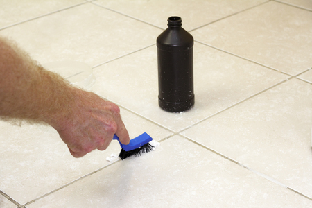 Hand with a blue handled black scrub brush cleaning grout with baking soda and peroxide. Floor grout tile being cleaned with baking soda and hydrogen peroxide. Stock Photo