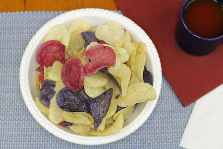 Three different colors of potato chips with tomato juice. Colorful red white and blue chips made from Crimson, Purple Majesty and Chipeta or Atlantic potatoes. Stock Photo