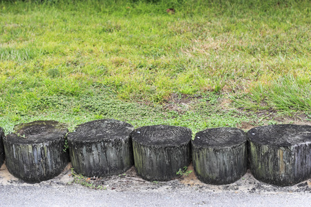 Wooden tree logs partly buried in the ground together as a wall to help prevent soil erosion. Part of a soil erosion barrier made from tree logs in a grassy area. Stock Photo
