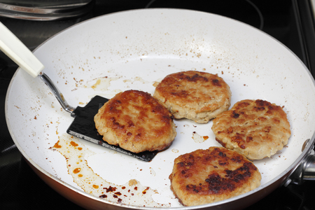 nonstick: Four ground turkey meat burgers cooked  in a non-stick pan on a stove top. A spatula lifting up one of four turkey burgers that were cooked in a frying pan.