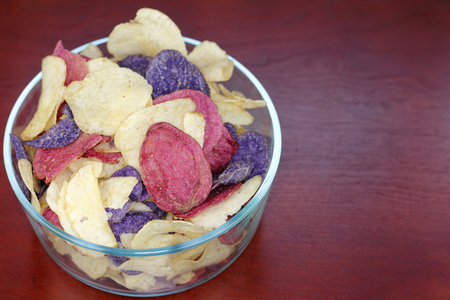Crimson, Yellow and Purple Potato ChipsCrimson, Purple Majesty and Chipeta or Atlantic potato chips in a glass bowl on a wood table. Potato chips variety mostly referred to as red, white and blue. Stock Photo