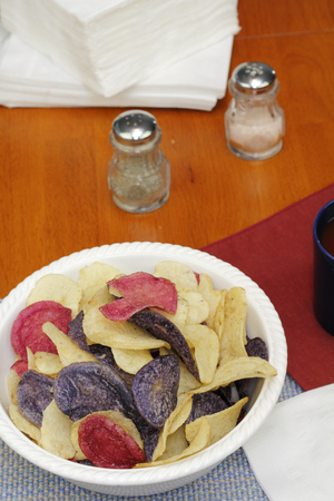 Bowl of three different colors of chips, red yellow and purple, usually referred to as red, white and blue. Variety of potato chips in a white bowl on a table. Stock Photo
