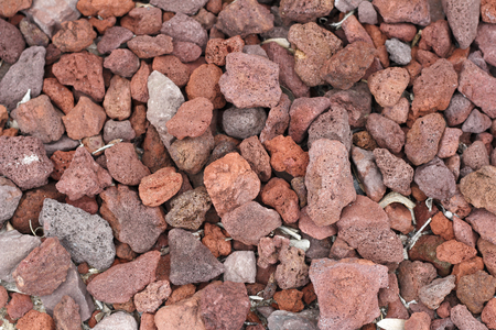 Many medium and small volcanic red rocks all together on the ground being used as ground cover. Red volcanic rocks ground cover background close-up outside in the day. Stock Photo