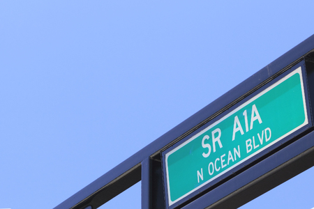 Outdoor green and white, painted metal, State Route A1A North Ocean Boulevard street sign. SR A1A N Ocean Blvd overhead on a public street sign post on a sunny blue sky day.