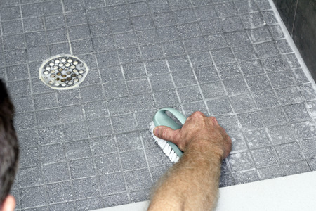 Male leaning into a shower, scrubbing a tile floor with a scrub brush and soap. Gray tile floor with grout being cleaned by an adult male with a scrub brush and soap.
