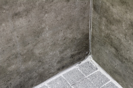 Grout in a home shower corner between wall and floor that is cracked and split. A domestic shower that has split grout in corner between the floor and wall tile.