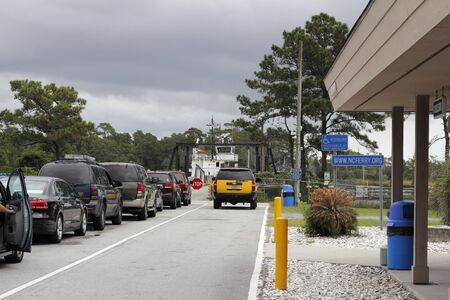 Southport, NC, USA - September 29, 2016: People in vehicles waiting to drive onto the Southport Ferry in the day. Autos with people ready to board the ferry.