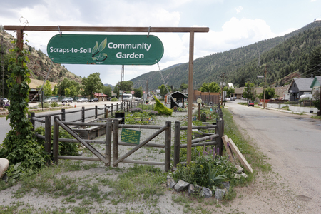 Idaho Springs, CO, USA - June 24, 2016: Beautiful Community Garden, Scraps-to-Soil and entry signs at 2225 Miner Street. Scraps-to-Soil Community Garden on a summer day