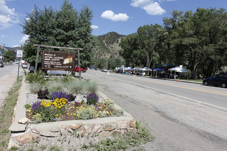 Idaho Springs, CO, USA - June 24, 2016: A sign welcomes visitors to historic colorado mining country. Merchant Farmers market in park across the street