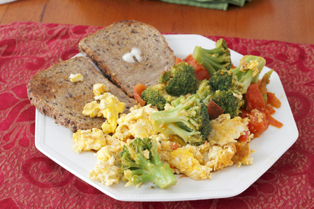 Octagon plate with breakfast food of scrambled eggs cooked with broccoli and tomatoes with buttered toast. Big breakfast of eggs, vegetables and toast.