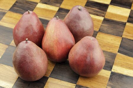 Five organic red pears close-up on a solid wooden inlay chess board background. Several organic red pears grouped together on a beige and brown wood chess board. Stock Photo