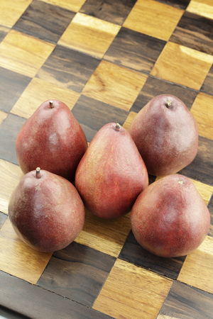 Five organic red pear fruit on inlaid wooden chessboard close-up.  Handmade inlay brown and beige wood chess set board with several organic red pears on its surface.