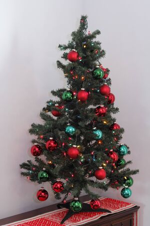 One short, artificial Christmas tree decorated with lights and ornament balls. Fake evergreen Christmas tree with ornaments and a variety of LED lights.