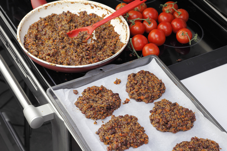 Parchment paper lined cookie sheet with quinoa and three bean patties ready to be cooked. Preparing tricolor bean and quinoa burgers recipe in the kitchen. Stock Photo