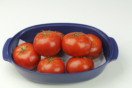 Many hydroponically grown red tomatoes grouped in an oblong blue bowl on a white quartz kitchen counter up close. Several red tomatoes with stems in a blue dish. Stock Photo