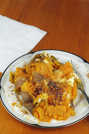 Cooked orange sweet potato chopped pieces with cinnamon and butter. Butter and cinnamon spiced sweet potato with orange flesh and brown skin on a plate.