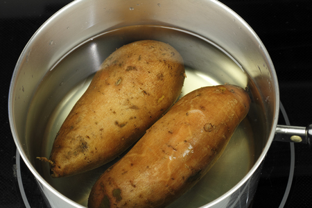 Preparing two orange sweet potatoes, ipomoea batatas, in a pan of water ready to boil. Close-up of two uncooked, whole sweet potatoes in water in a deep stovetop pot