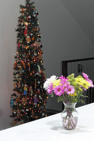 Inside a home at night a beautiful floral bouquet in a vase with a decorated a Christmas tree. Vibrant flowers bouquet and Christmas tree in the background. Stock Photo