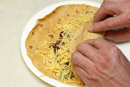 Hands preparing lunch of sun dried tomato soft wrap filled with beans, cheese and guacamole. Close-up of two male hands wrapping a vegetarian burrito on a plate Stock Photo