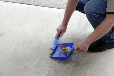 Male crouched down sweeping a cement garage floor of dust and debris with a small broom into a dustpan. Rubbish on a garage floor being swept into a dustbin by a man Stock Photo