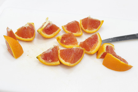 One bright orange fruit cut into twelve pieces with a knife on a white plastic cutting board close-up. An orange sliced into many chunks on a cutting board.