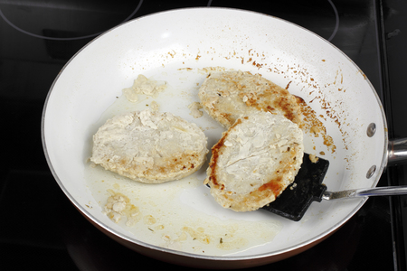 Three turkey burgers being cooked in coconut oil with a non-stick stovetop pan. Black spatula turning one turkey patty being cooked saucepan with coconut oil