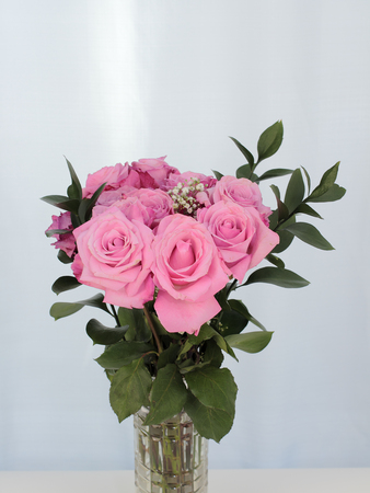 cutglass: Vibrant pink rose flowers bunch in a cut-glass vase with a subtle background. Green leaves and baby's breath accent pink bouquet of roses in a clear glass vase.