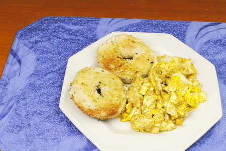 Scrambled eggs with mustard and toasted buttered everything bagels. Breakfast of everything bagels toasted and buttered with scrambled eggs with mustard Stock Photo