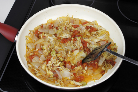 Mixed white onions, napa cabbage, red tomatoes and garlic cooking in a saucepan. Savory vegetables to serve with dinner cooking in a pan on a stove.