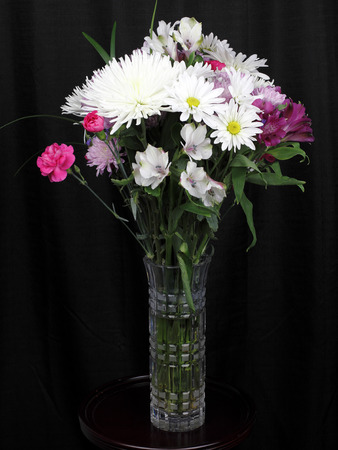 Black curtain behind a tall cut glass vase of colorful flowers and leaves. White, pink and violet flowers in a vase close-up in front of a black curtain.