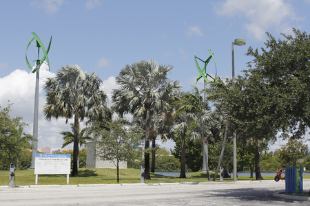 Fort Lauderdale, FL, USA - May 16, 2017: Wind turbines and electric vehicle power charging station in Mills Pond Park. EV charging stations and urban wind turbines