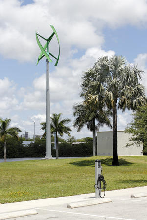 Fort Lauderdale, FL, USA - May 16, 2017: Urban wind turbine with an EV charging center. Electric vehicle charging center with a wind turbine.