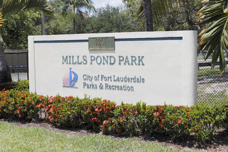 Fort Lauderdale, FL, USA - May 16, 2017: Large entry signage with red flowers at the entrance to Mills Pond Park. Front sign in landscaped Mills Pond Park on a sunny day