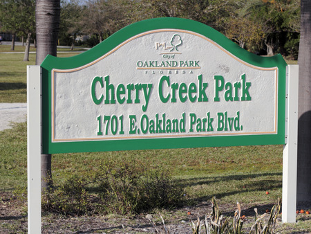 Oakland Park, FL, USA - March 10 2017: Green, white and yellow Cherry Creek Park sign outside on a sunny day. Cherry Creek Park in Oakland Park, Florida one winter day