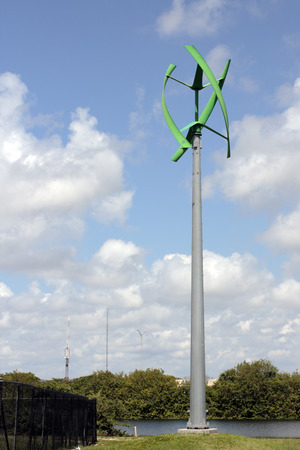 One Green Urban Wind Turbine, Fort Lauderdale, FL, USA - May 16, 2017: Green color power generating wind turbine near a park lake. Unusual vertical access wind turbine outside in Mills Pond Park.