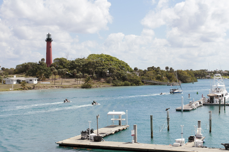 Jupiter, FL, USA - March 30, 2017: Boat docks and people on jet skis, boats and paddle boards in the Loxahatchee River. People on watercraft on Jupiter Inlet near a lighthouse. Editorial