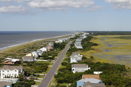 Distant aerial view of Oak Island, NC coastal living homes road, marsh and more in the summer. Day high view of homes and more at Atlantic coasts Oak Island. Stock Photo