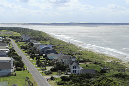Fort Caswell and Bald Head Island seen from a high view on a sunny day. Scenic high view of the Atlantic Ocean seascape and landscape with homes of Caswell Beach   Editorial